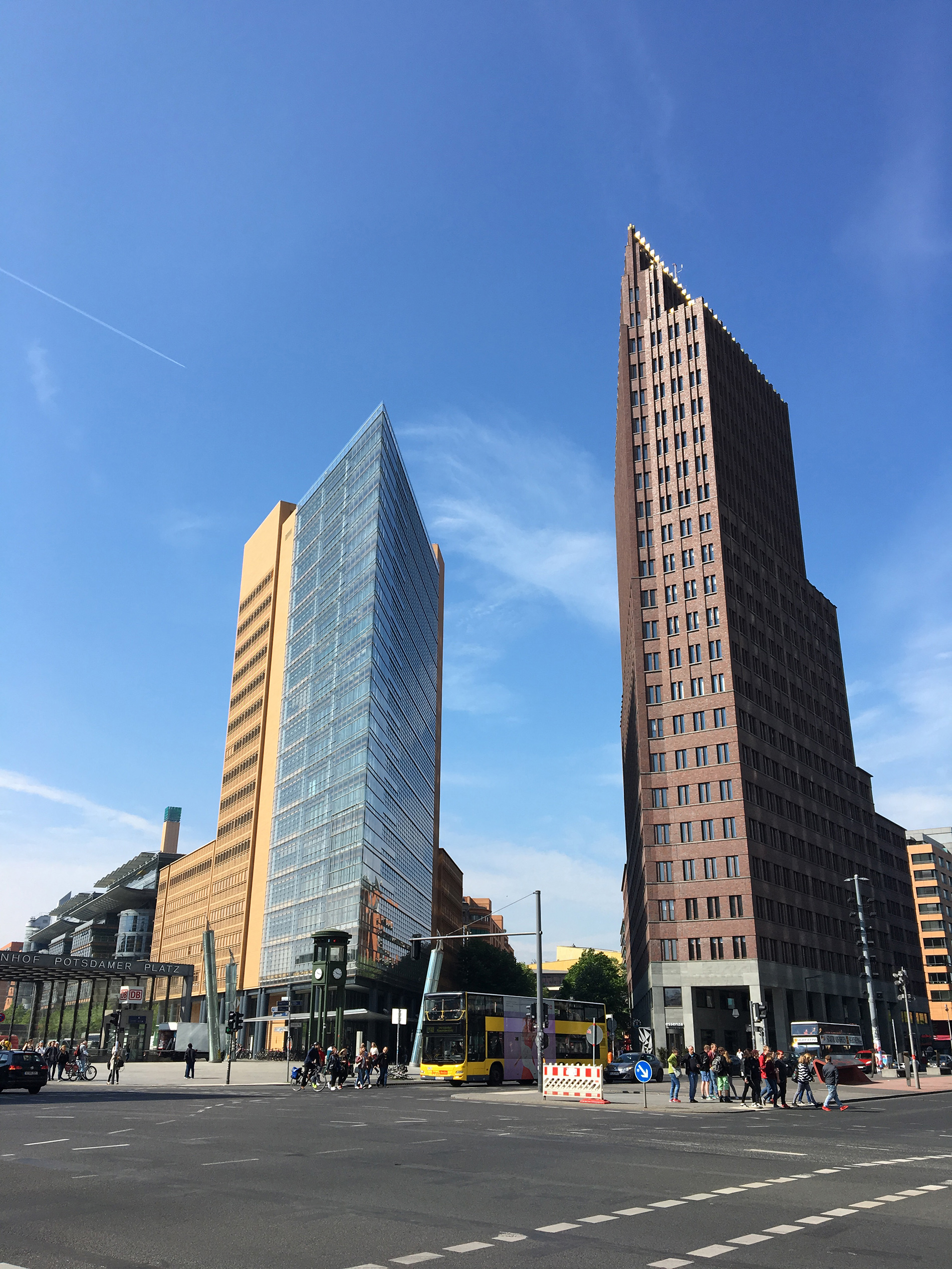 Upward view of the a large brown building that is under a blue sky with a jet stream in the distance
