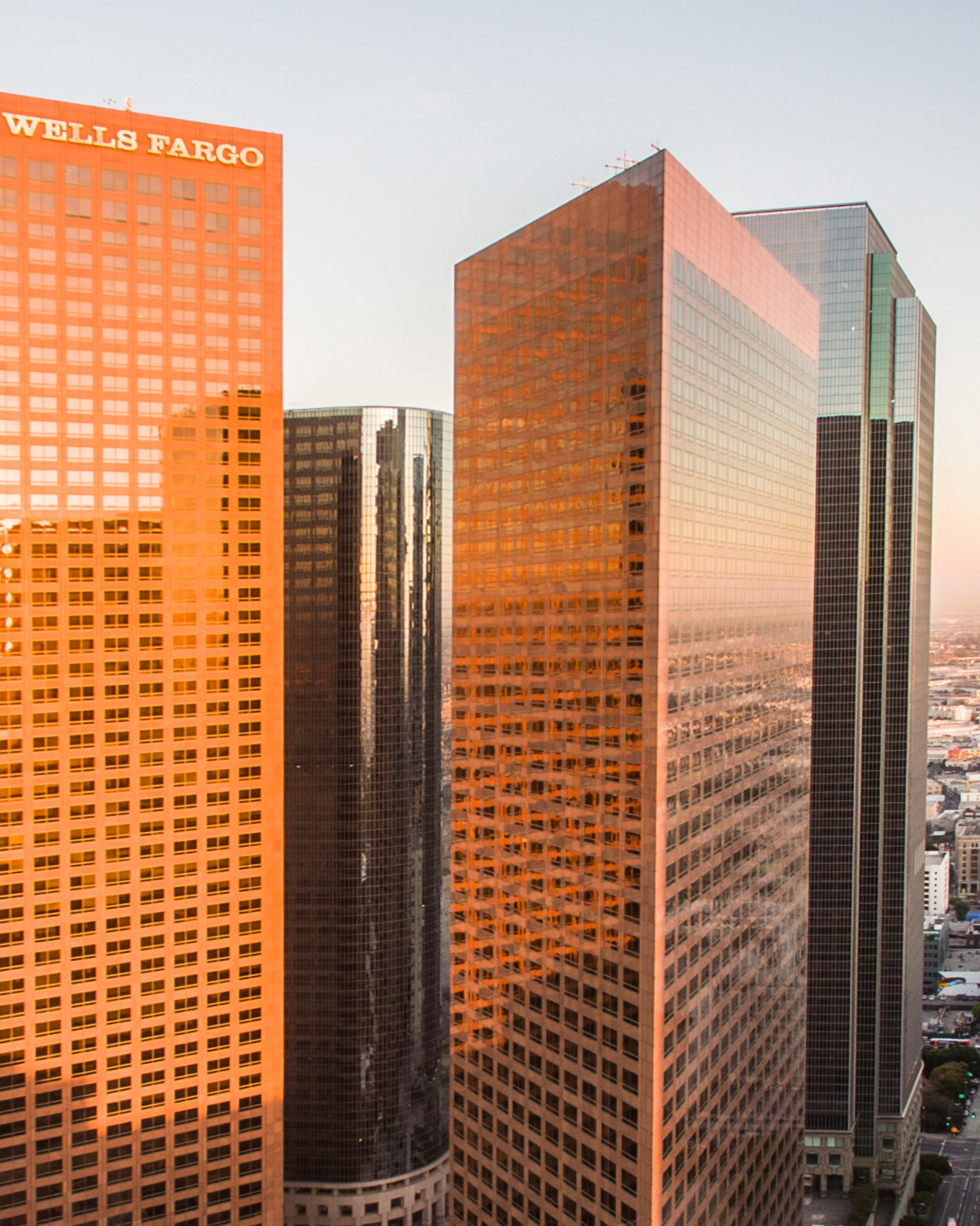 Image of several skyscrapers. Two red buildings are in the center, while the sun reflects off one behind them.
