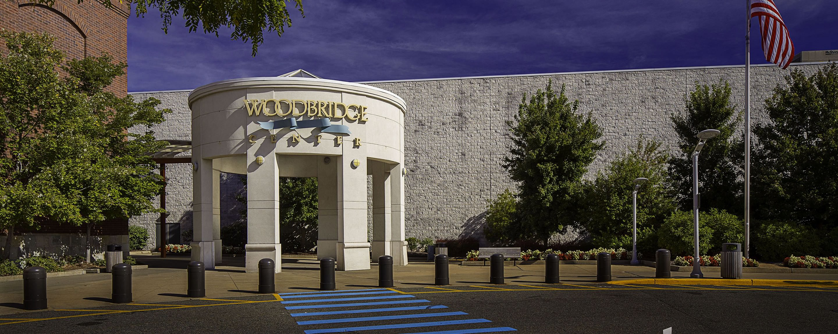 "A large sign reads ""Woodbridge Center."" It stands in front of a large white building."