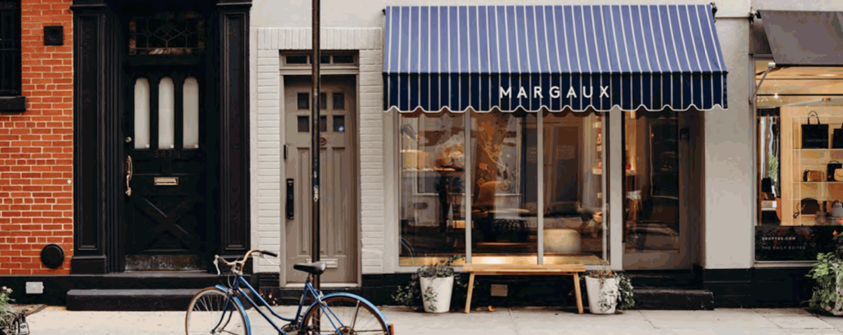 A storefront with a white and blue sign that says Margaux. A blue bicycle sits in the foreground.