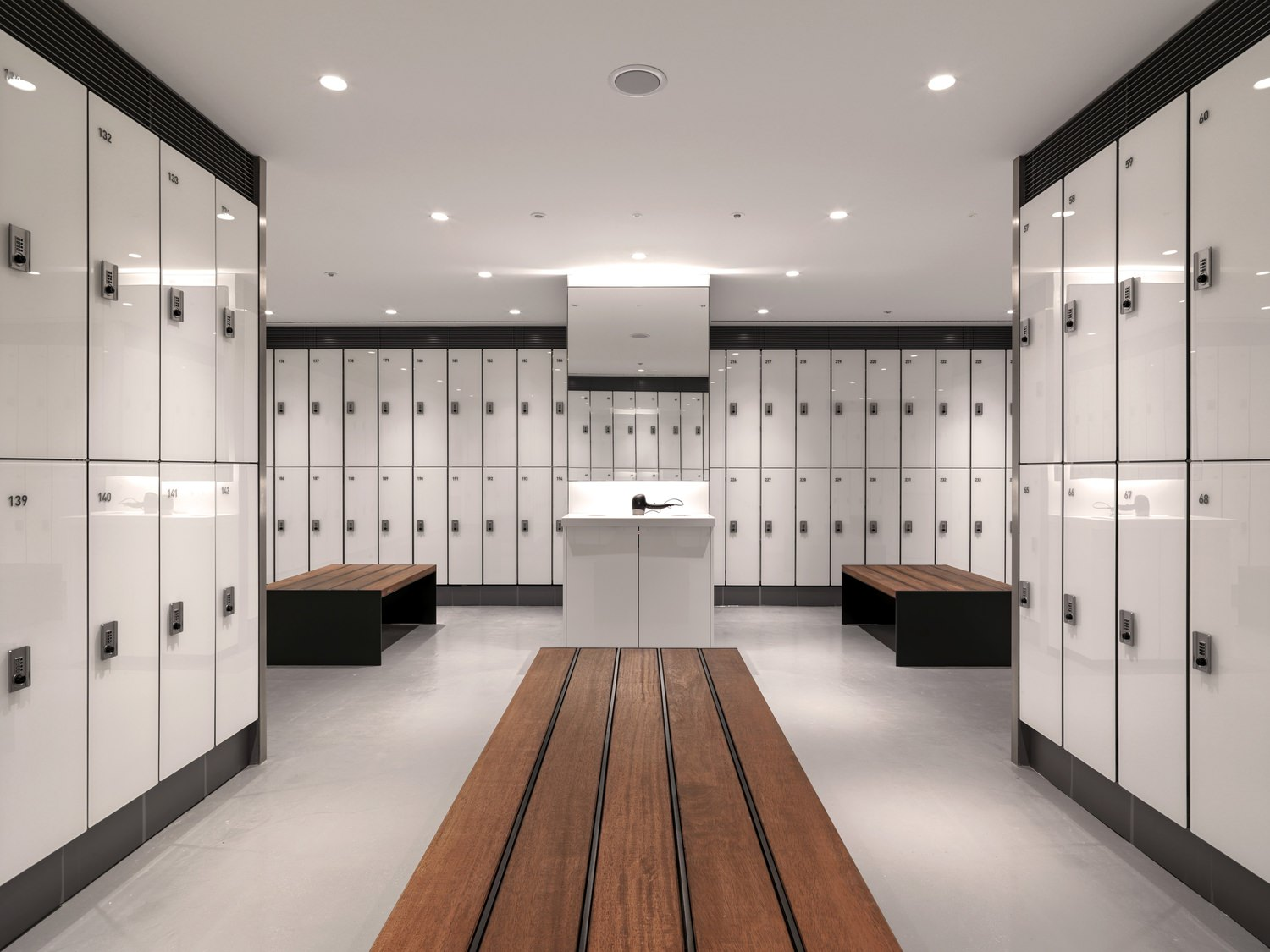 Large room with white tiles and rows of wooden benches next to white lockers cabinets.