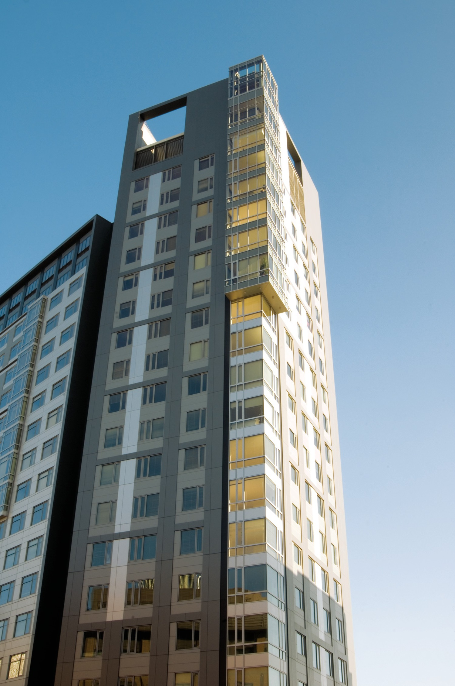 A large apartment building that is next to a tower under the blue sky in the city.