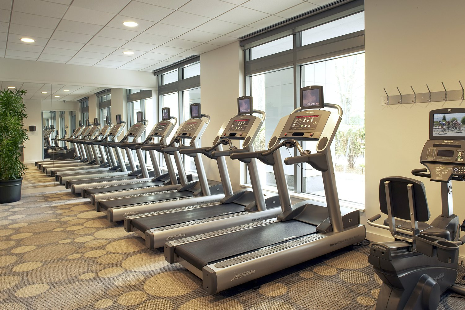 A row of treadmills and other exercise machines inside of a gym with tiled floors.