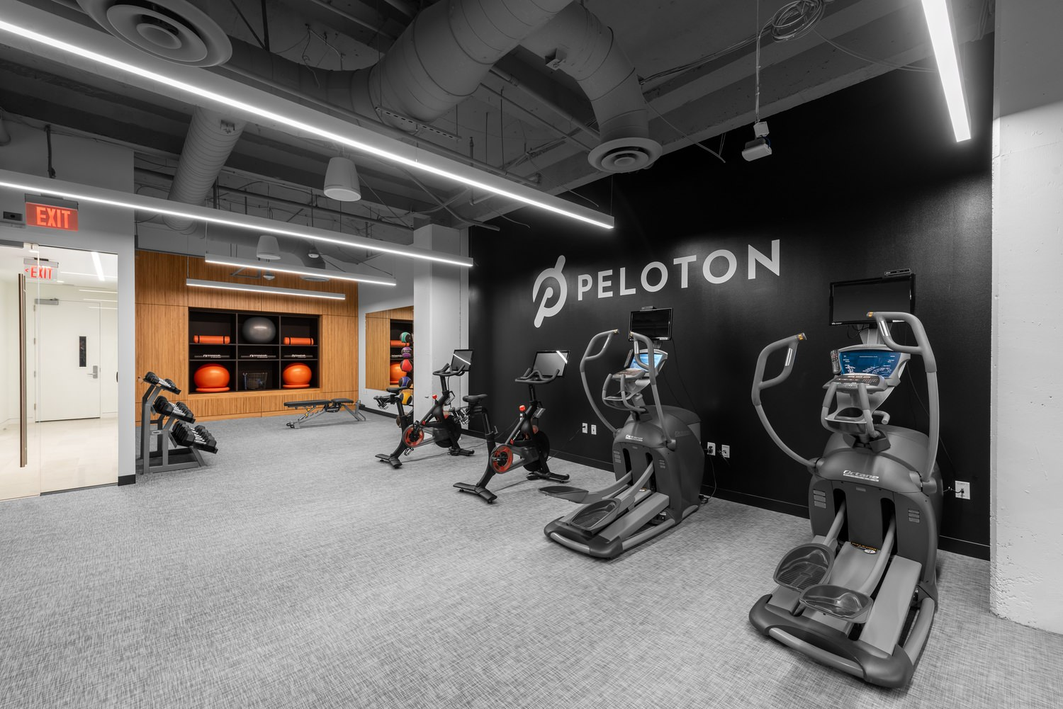 A gym that has stationary bicycles as well as elliptical machines and the word peloton is on the wall.
