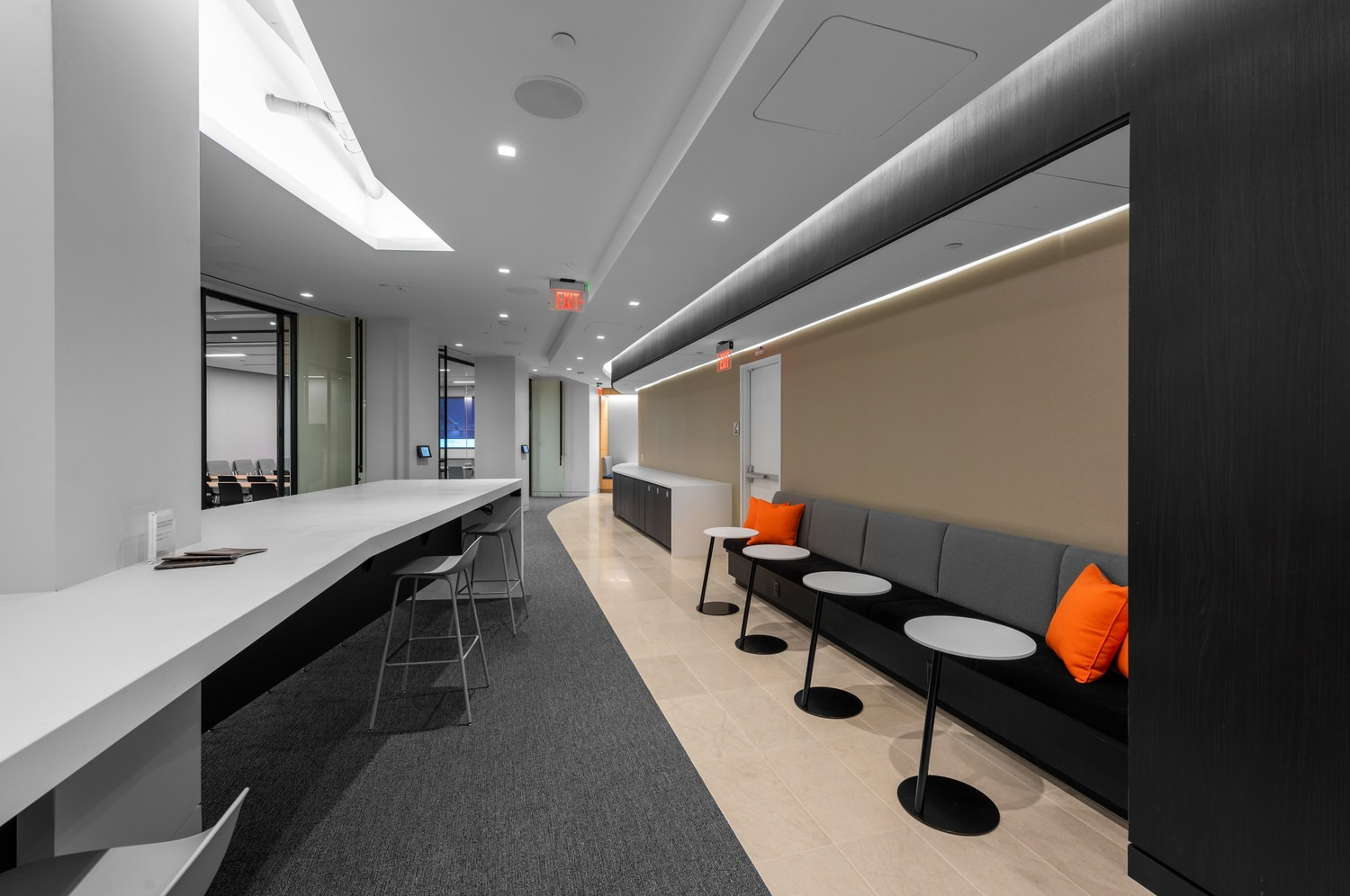 Break room with tables and chairs lined along the wall near some glass sliding doors.