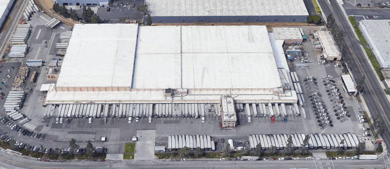 A large ware house that has many semi trucks that re in the parking lot and in the loading docks.