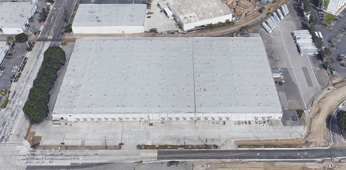 Top view of a big building with a white roof that is surrounded by cars parked in the lot around it.