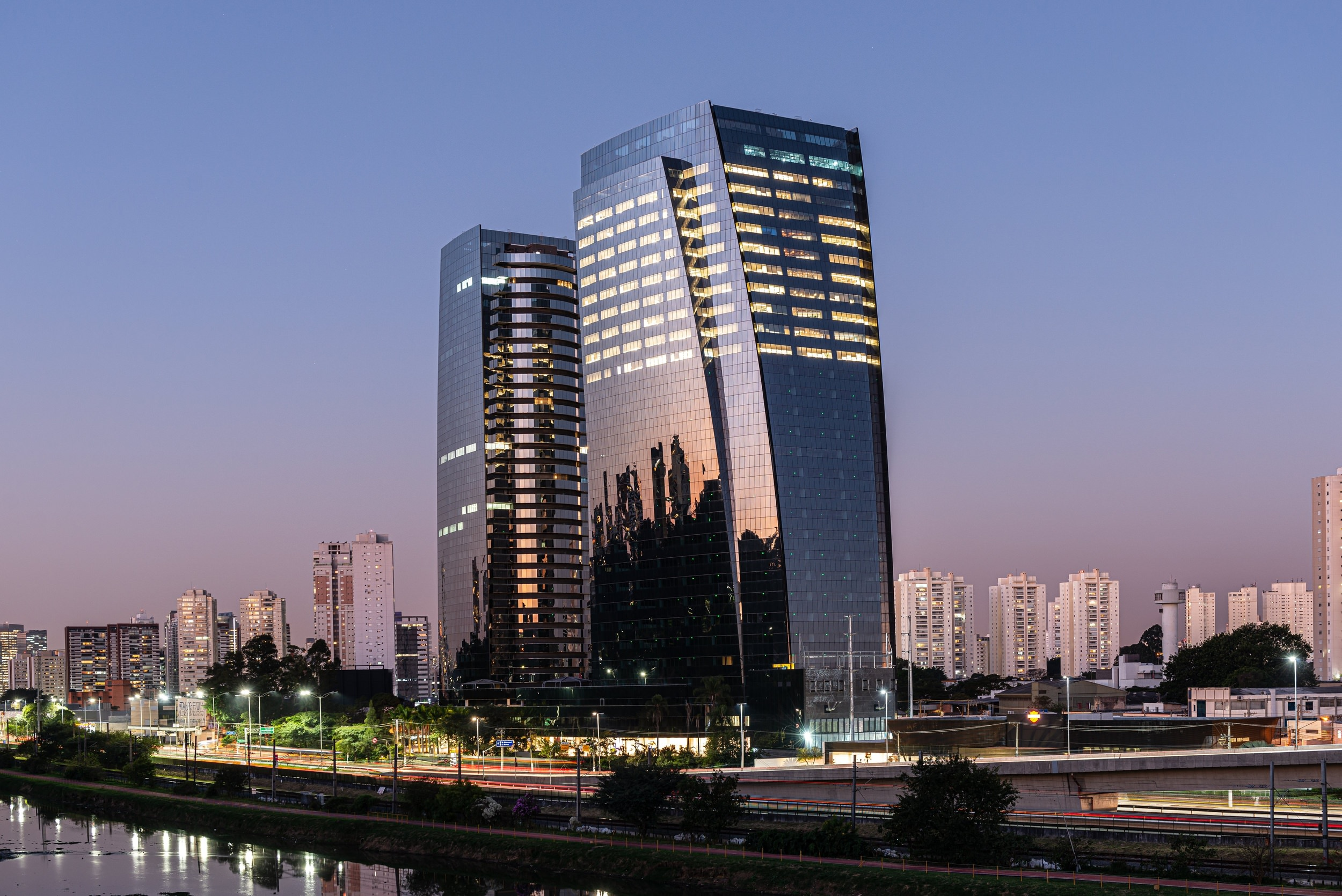 Two modern glass and steel towers that are curved and alongside a river and have the lights turned o