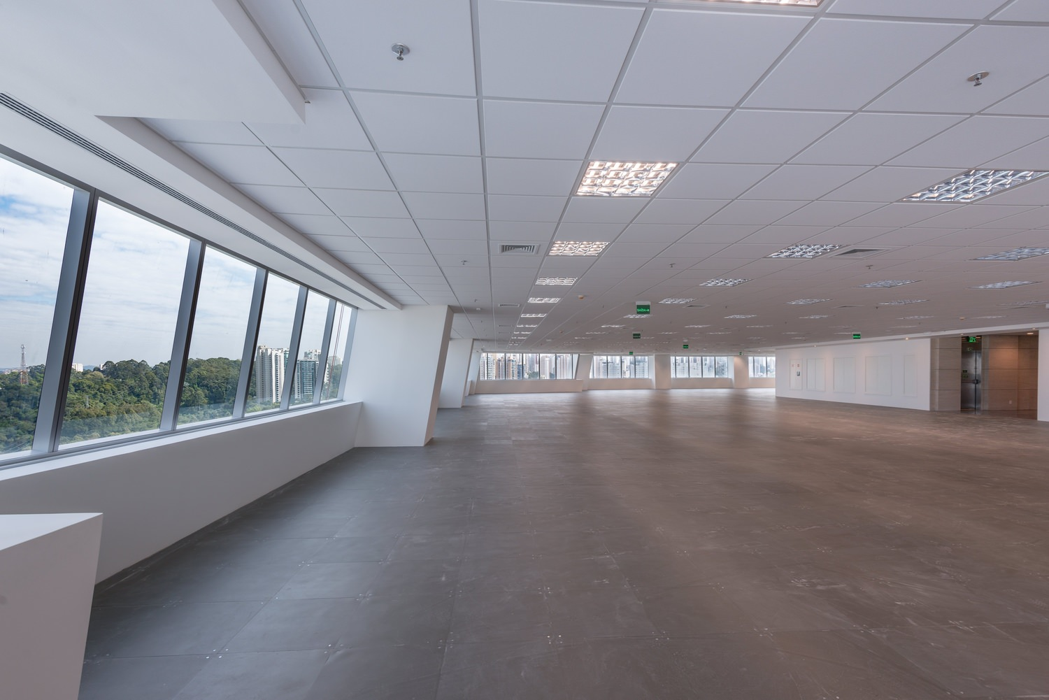 A large empty room with white ceiling panels and walls that has windows lining the sides.