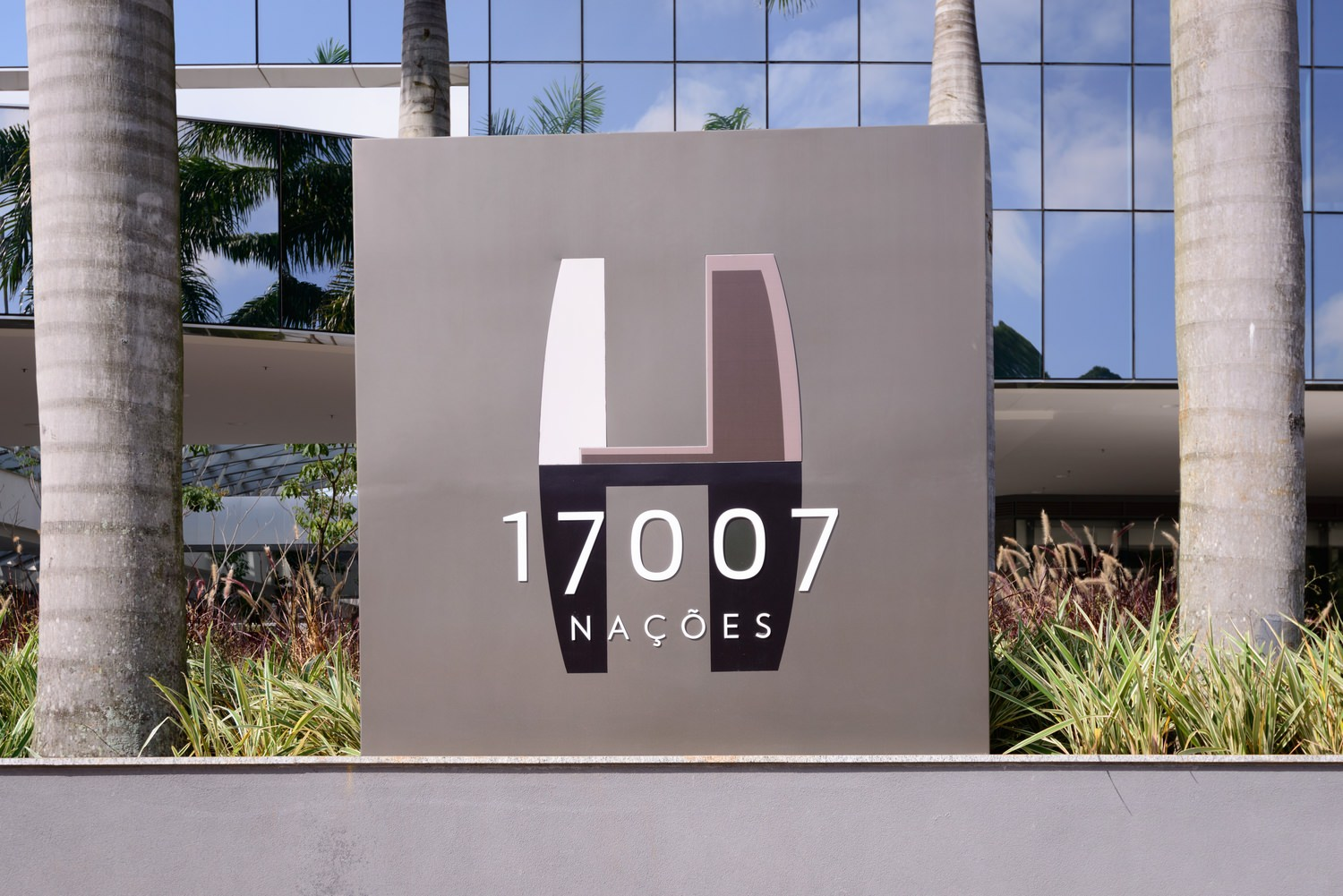 A sign that is in front of a building and the sign says 17007 Nacoes on it and plants next to it.