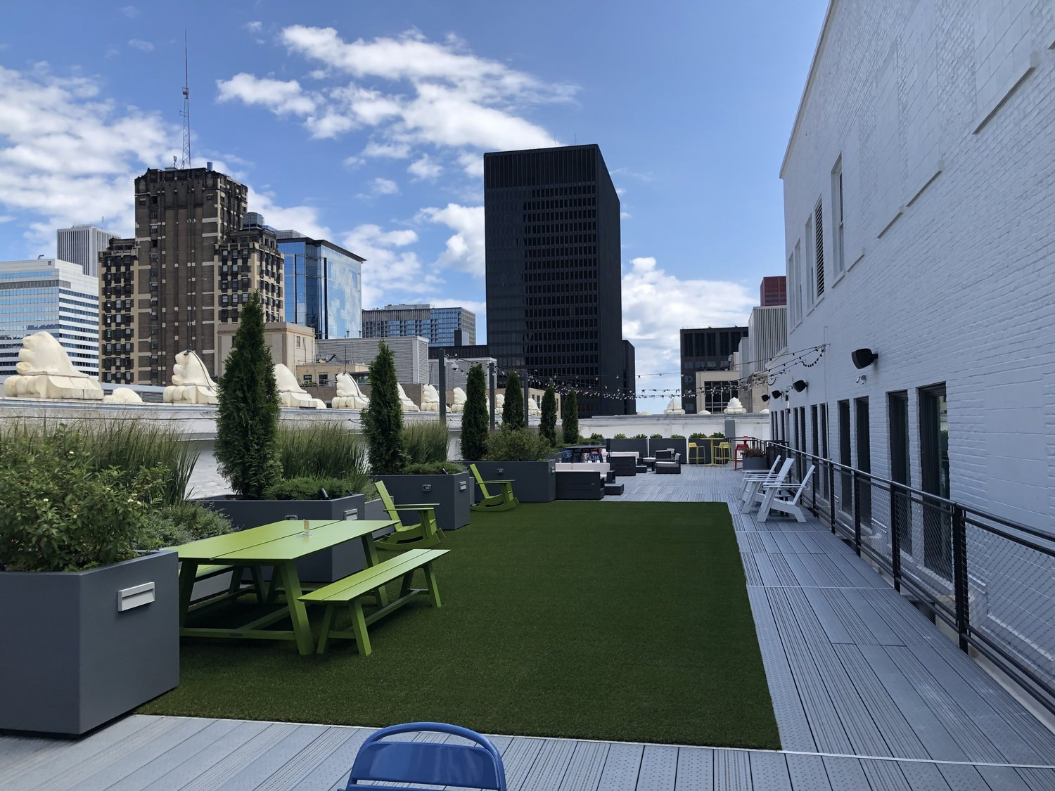 A courtyard that has grass and outdoor furniture that is on top of a building in the middle of a city.