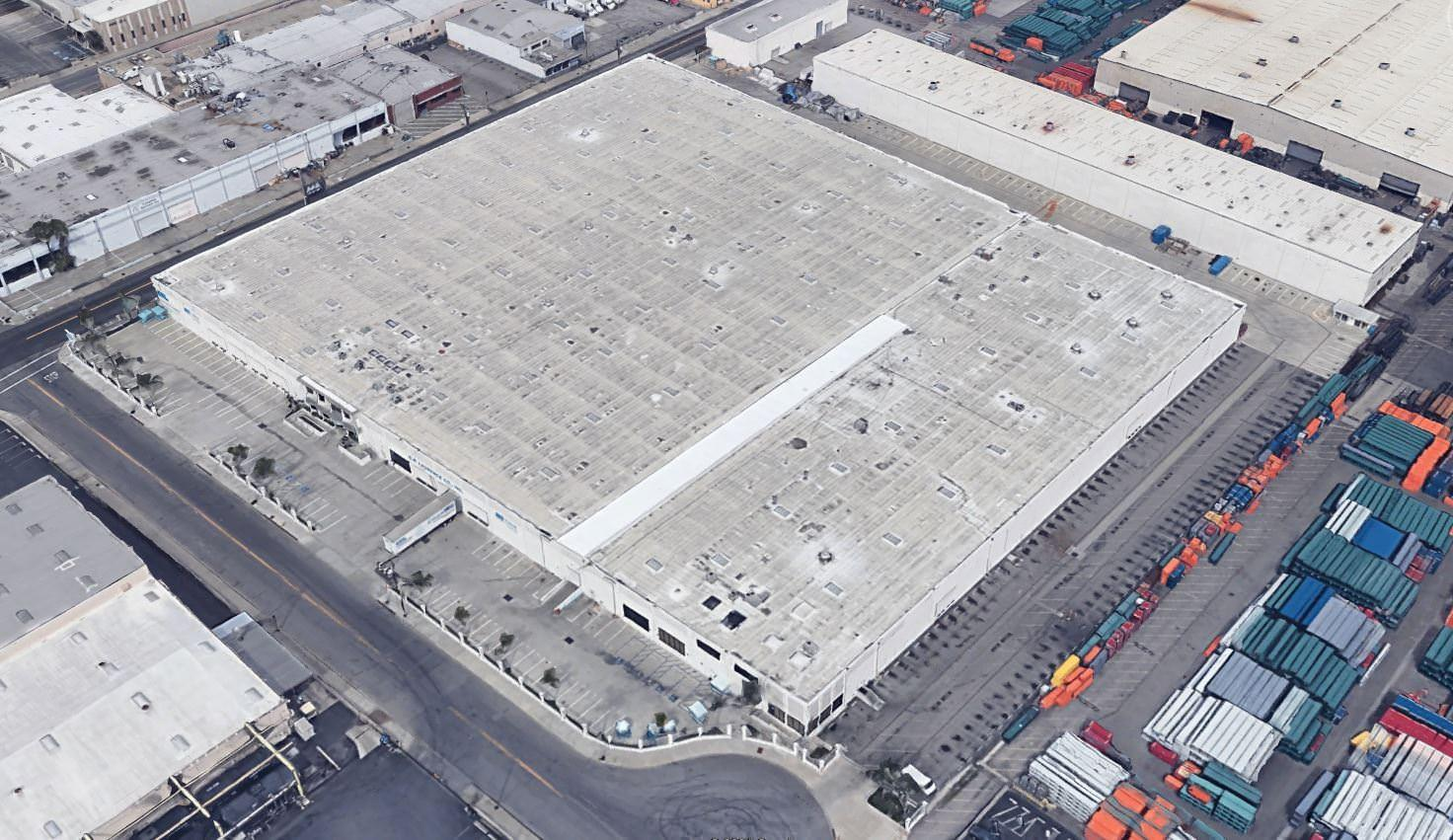 An aerial view of a warehouse that has trucks around it as well as a big parking lot near it.