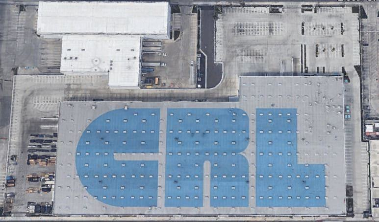 A parking lot full of cars that is next to a building with the letters CRL printed on the white roof