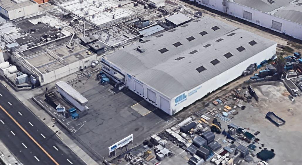 An aerial view of a warehouse that has a lot of cars and vehicles around the front of it.
