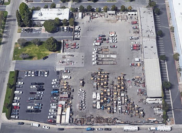 Top view of a parking lot that is full of cars and lawns with trees lining the area.