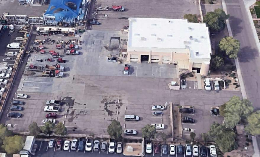 A building with a parking lot that is full of vehicles and rundown trucks by the street.