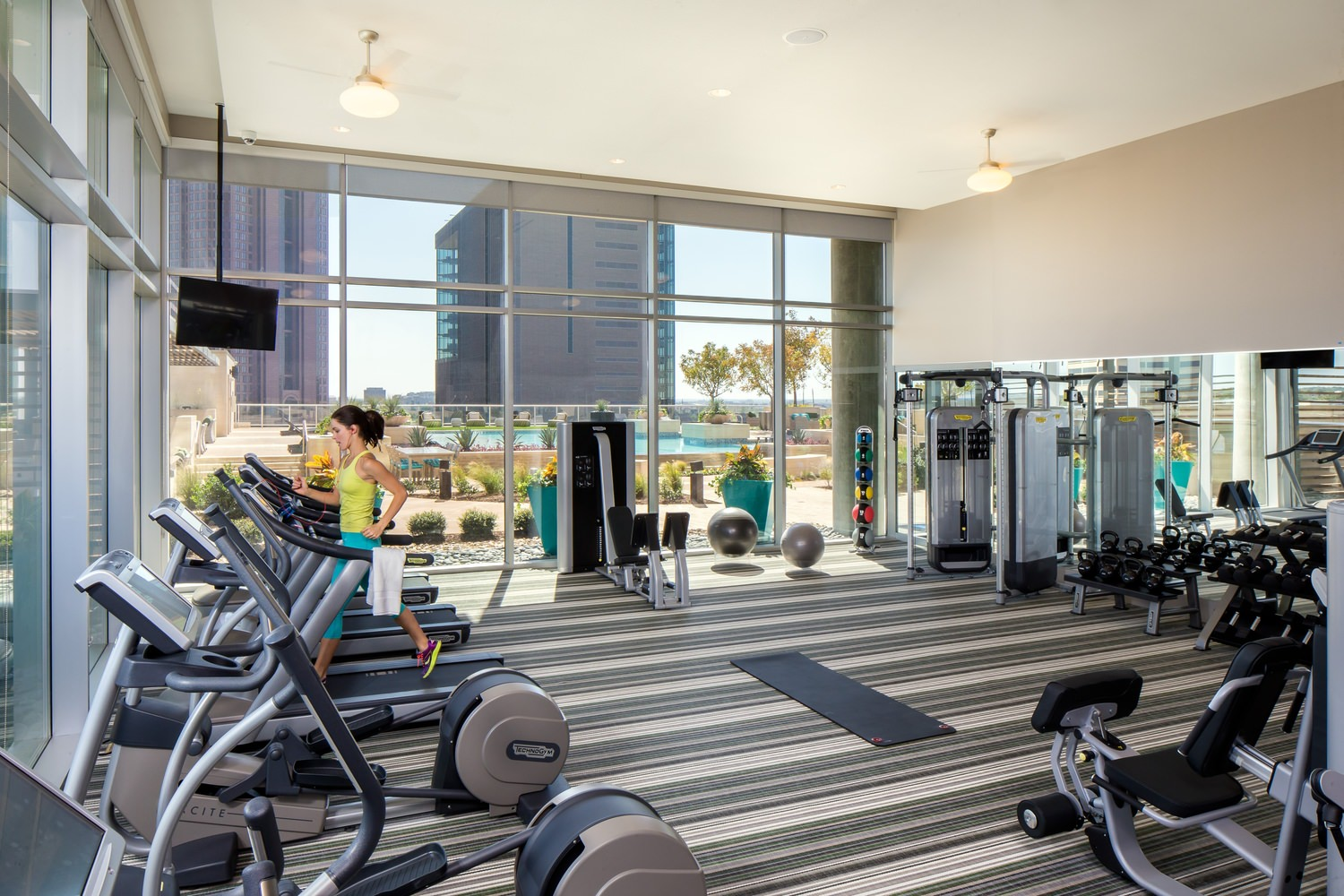 An indoor view of a gym where there are bicycles, treadmills, and strength training equipment.