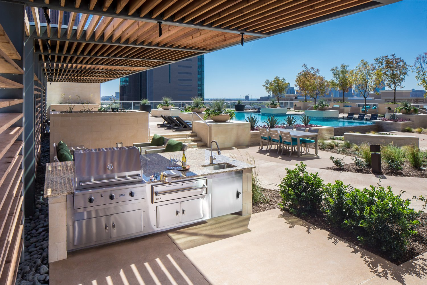 Outdoor pool area with appliances and furniture that is next to some buildings.