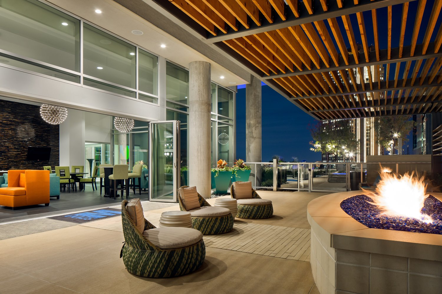 A large lounge area that is full of outdoor furniture next to a fire pit under a gazebo.
