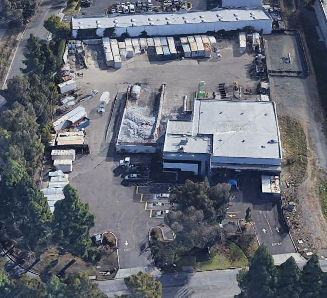 An aerial view of a warehouse and workshop that are near each other with parking lots all the way ar