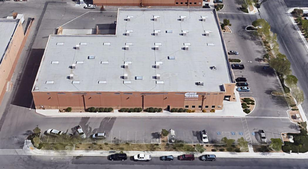 An aerial view of a large retail store that has a big parking lot around the front and side of it.