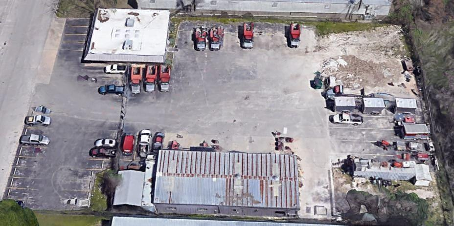 A group of small buildings that is surrounded by a parking lot full of cars and trucks.