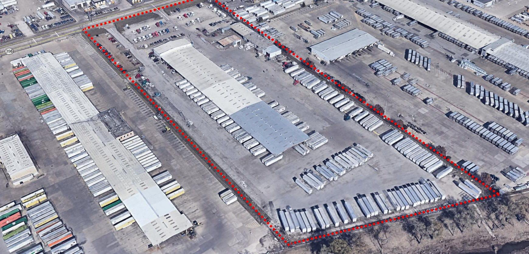 A warehouse that has a lot of semi trucks parked in the parking lot around it and containers behind
