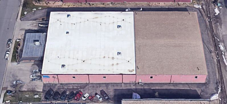 A warehouse that has a parking lot around it with cars sitting next to it and a road to the left of