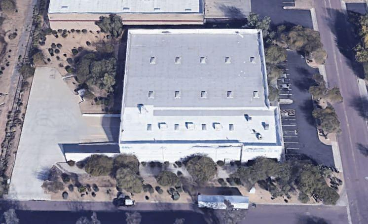 A top view of a building with a white roof that is surrounded by a parking lot full of cars.