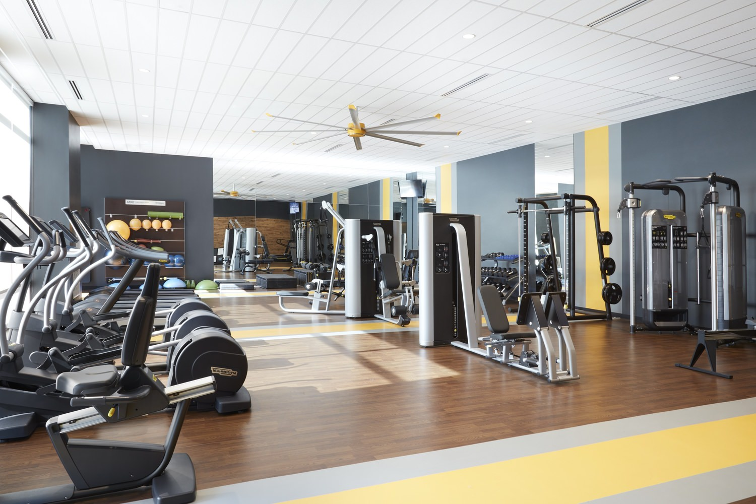 The inside view of a gym that has elliptical machines as well as some strength training machines.