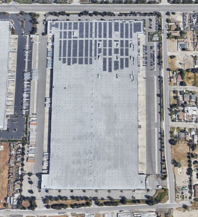 Top view of a warehouse that is surrounded by a parking lot full of trucks and cars.