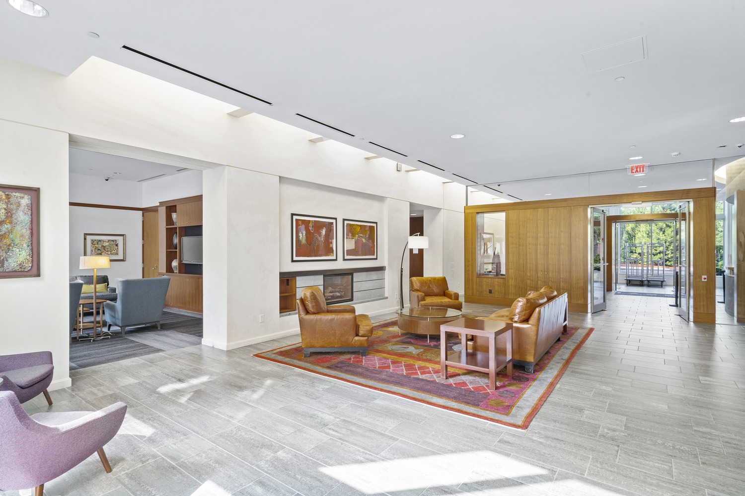 An empty lobby of a building that is full of furniture with a set of glass doors.
