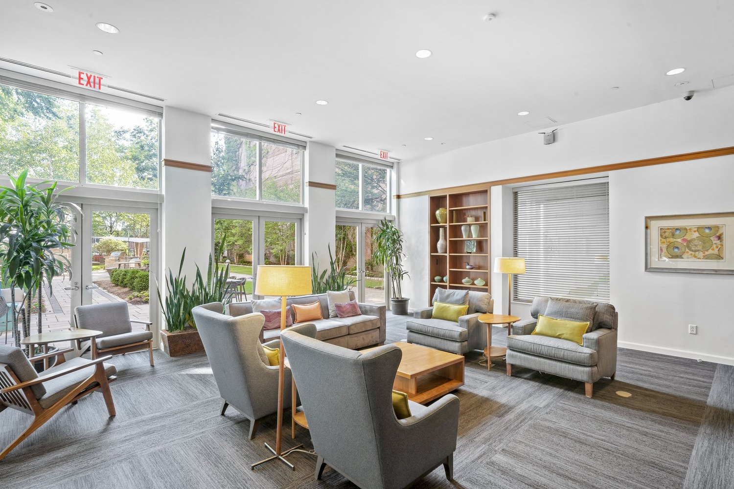 Lobby inside a building that has grey couches and other furniture with a glass wall that gives a view of the courtyard.