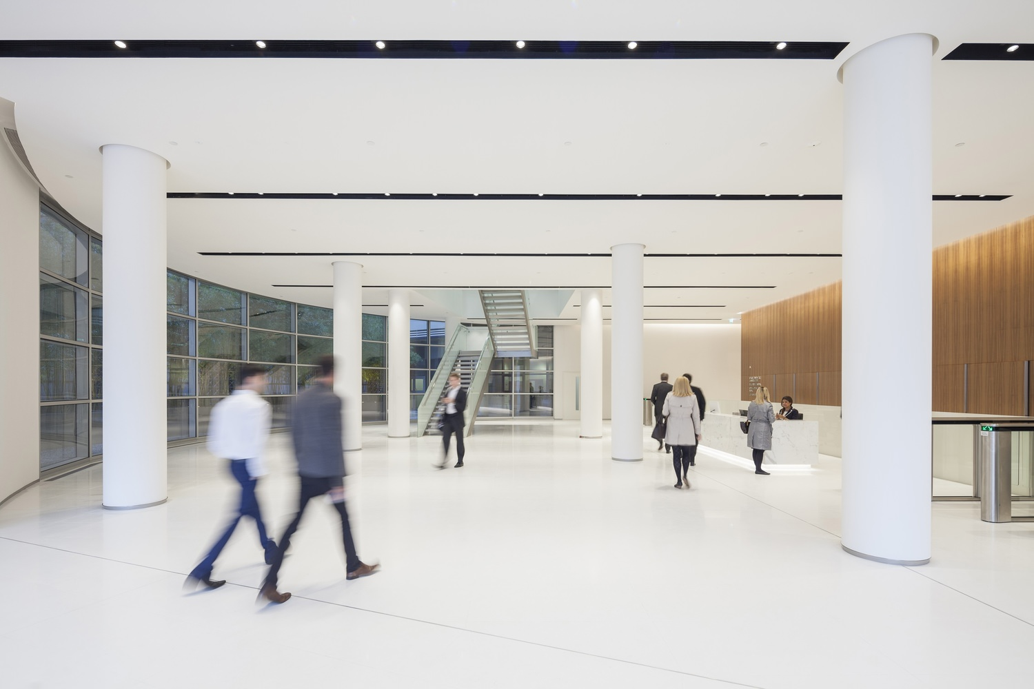 A small group of people in business attire walking along the lobby that has white columns and tiles.