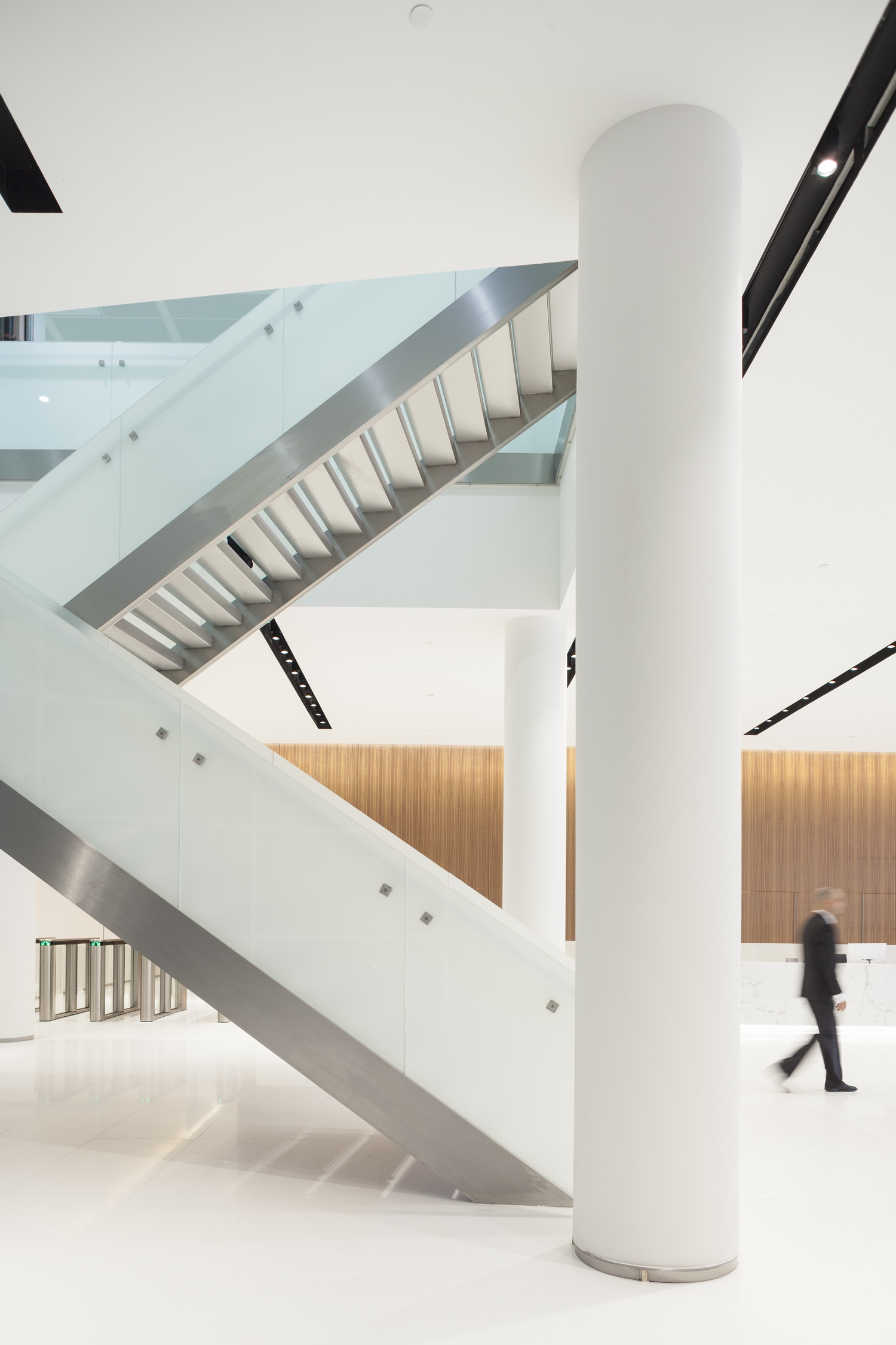A staircase that leads up from a lobby to another level and there are large white pillars next to it.