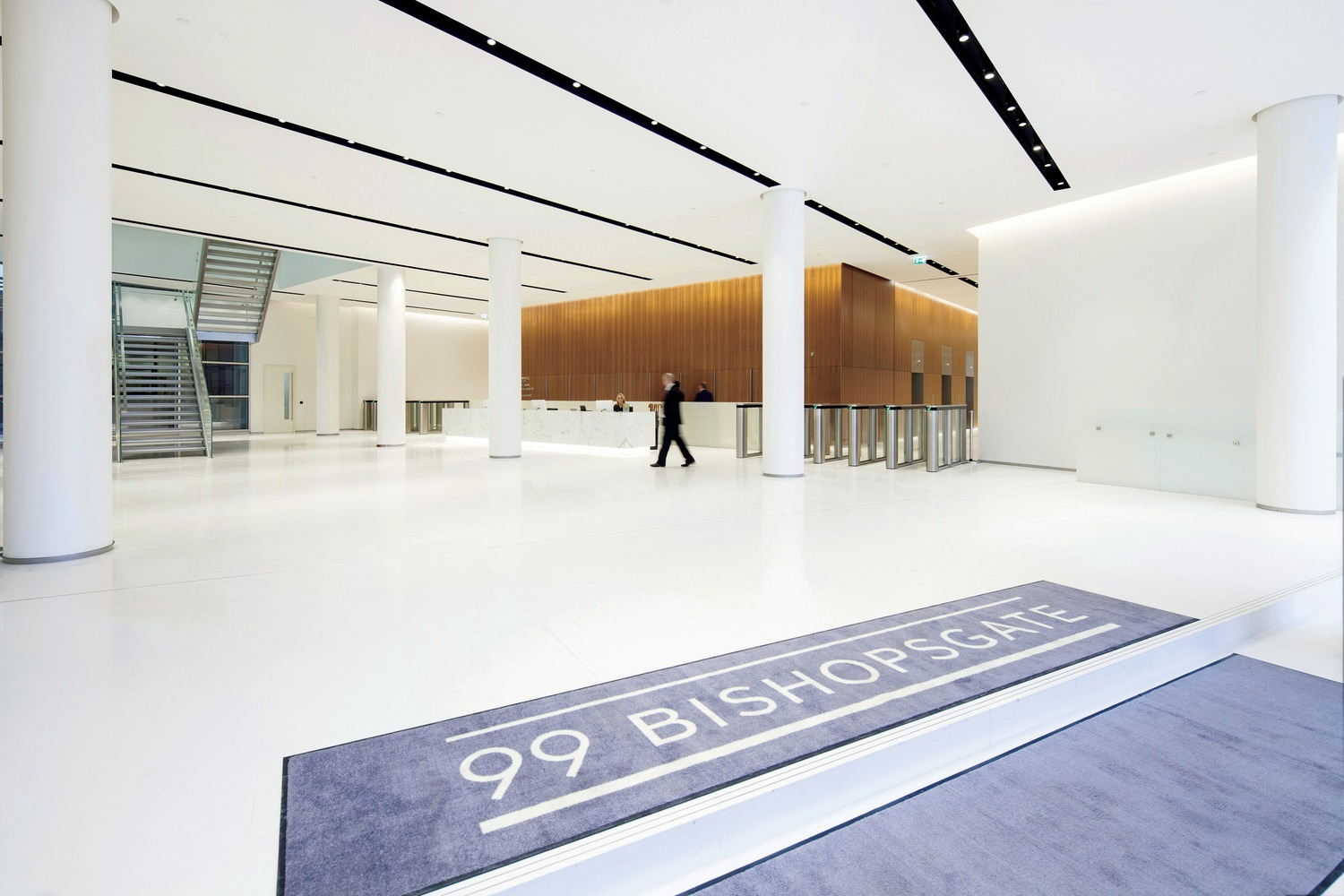 A large white lobby with a man walking through it. There's a blue rug in the foreground that says 99 Bishopsgate.