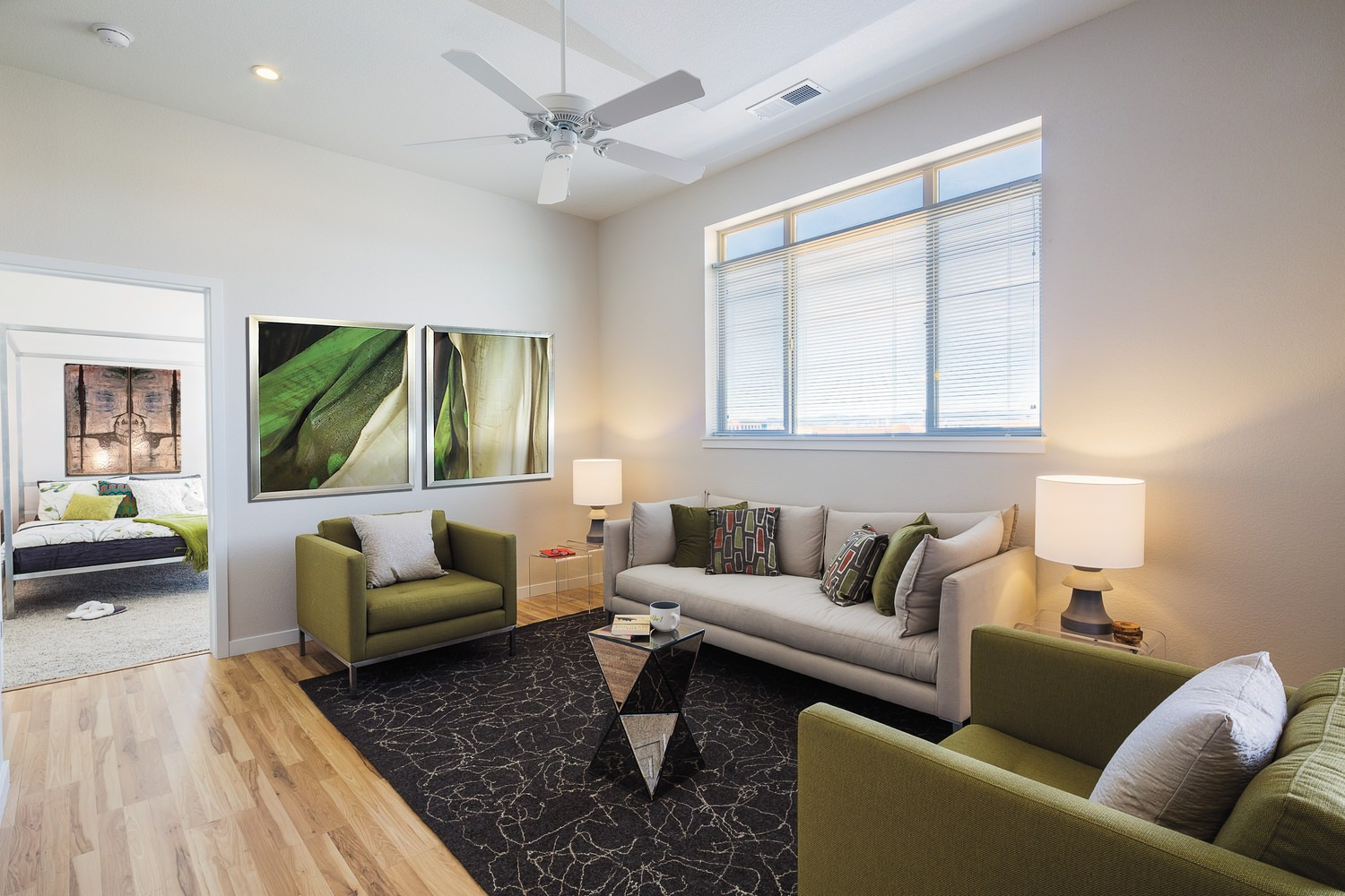 A living room that has green chairs and a grey couch in it and there is a bedroom off in the background.