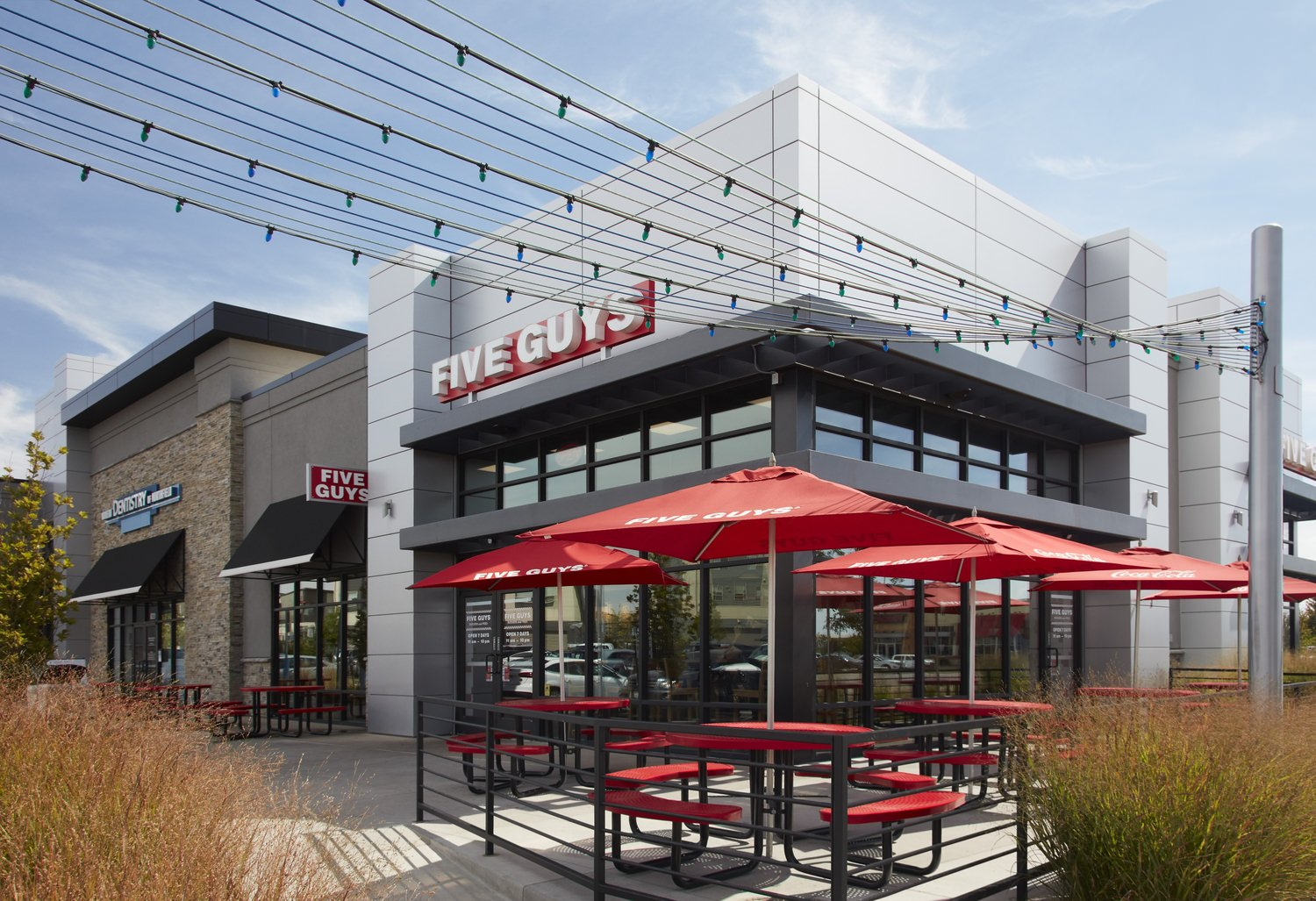 Outdoor patio of a Five Guys restaurant that has red tables and chairs with umbrellas.
