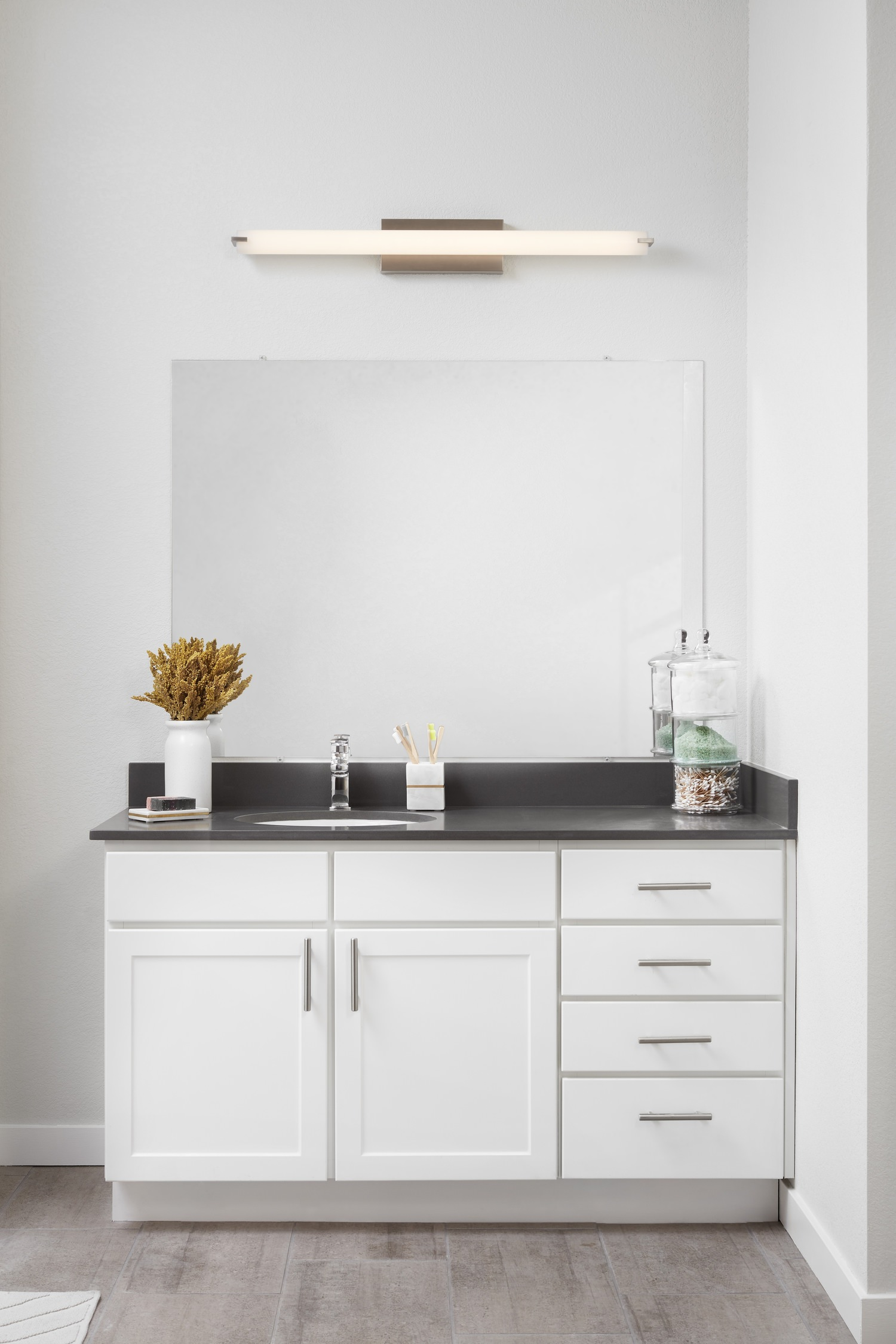 A bathroom vanity that has a sink and white cabinets with black countertops and a light above it.