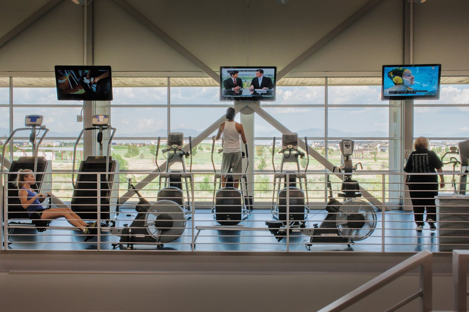 A group of people that are working out in a gym on elliptical machines and rowing machines.