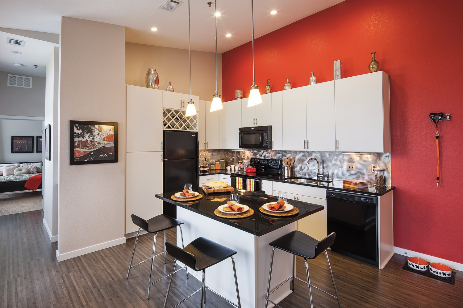 A small kitchen that has chairs around the island, white cabinets, and black appliances with red painted walls.