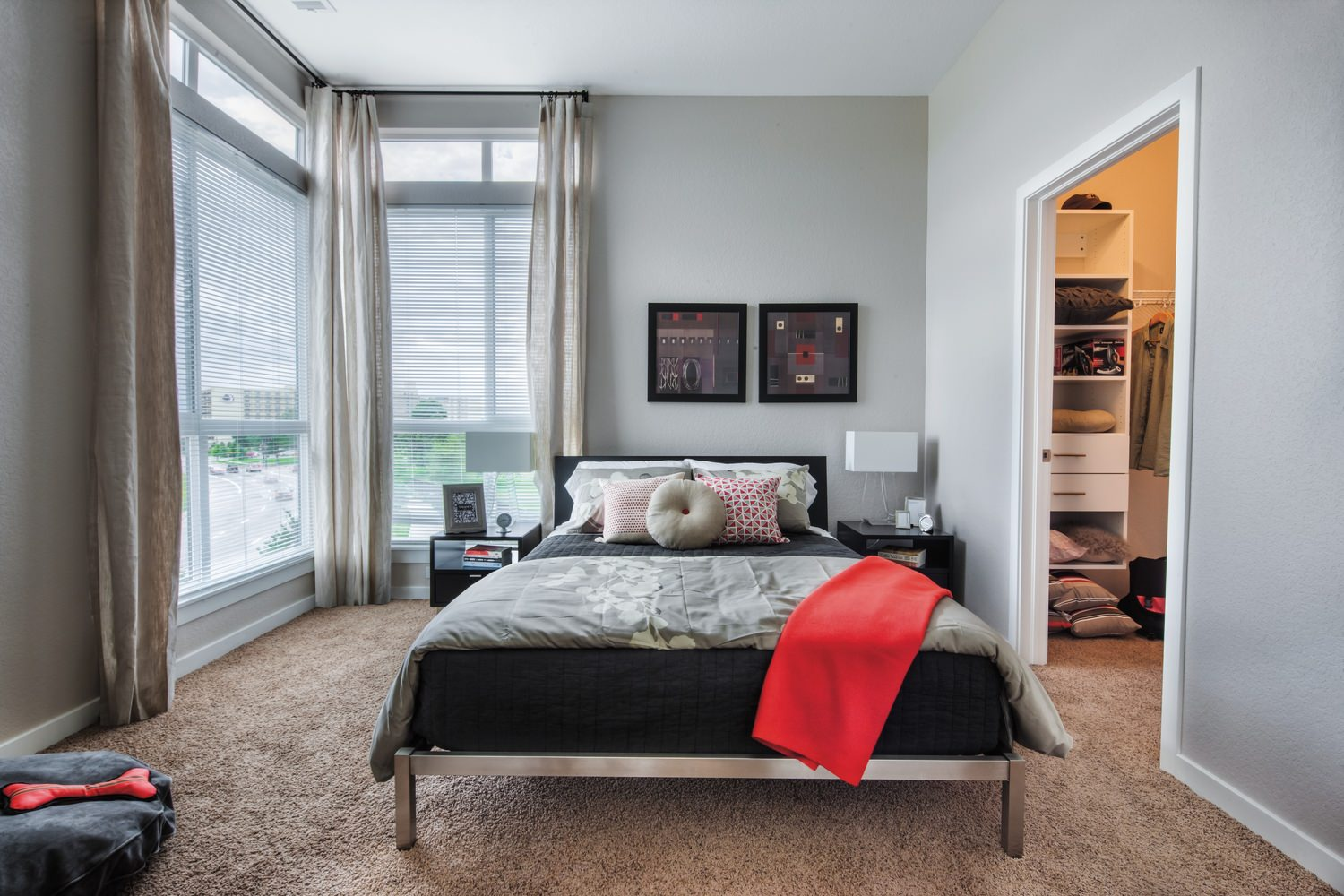 A bedroom full of furniture like a bed with grey sheets that is next to a large window.