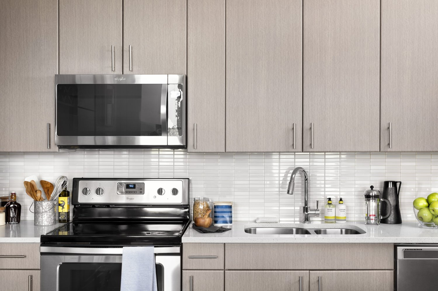 A view of a kitchen with light gray cabinets and stainless steel Whirpool appliances.