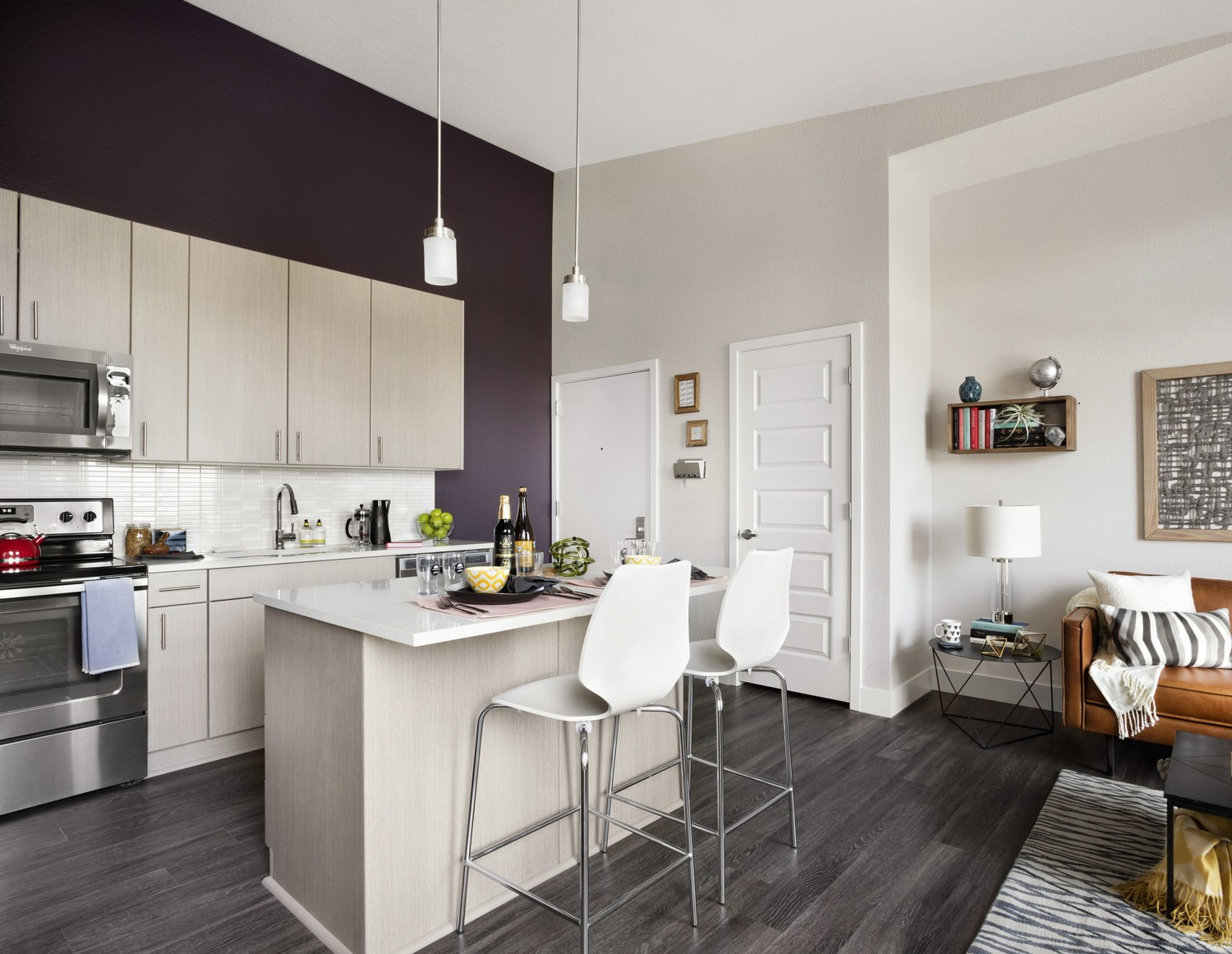An open kitchen with a tall center island and stainless steel appliances.