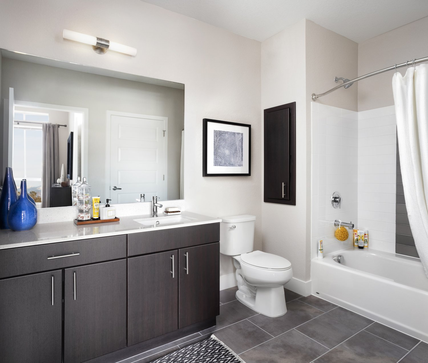 A bathroom in a house that has dark cabinets, a toilet, and a bathtub and shower combination.