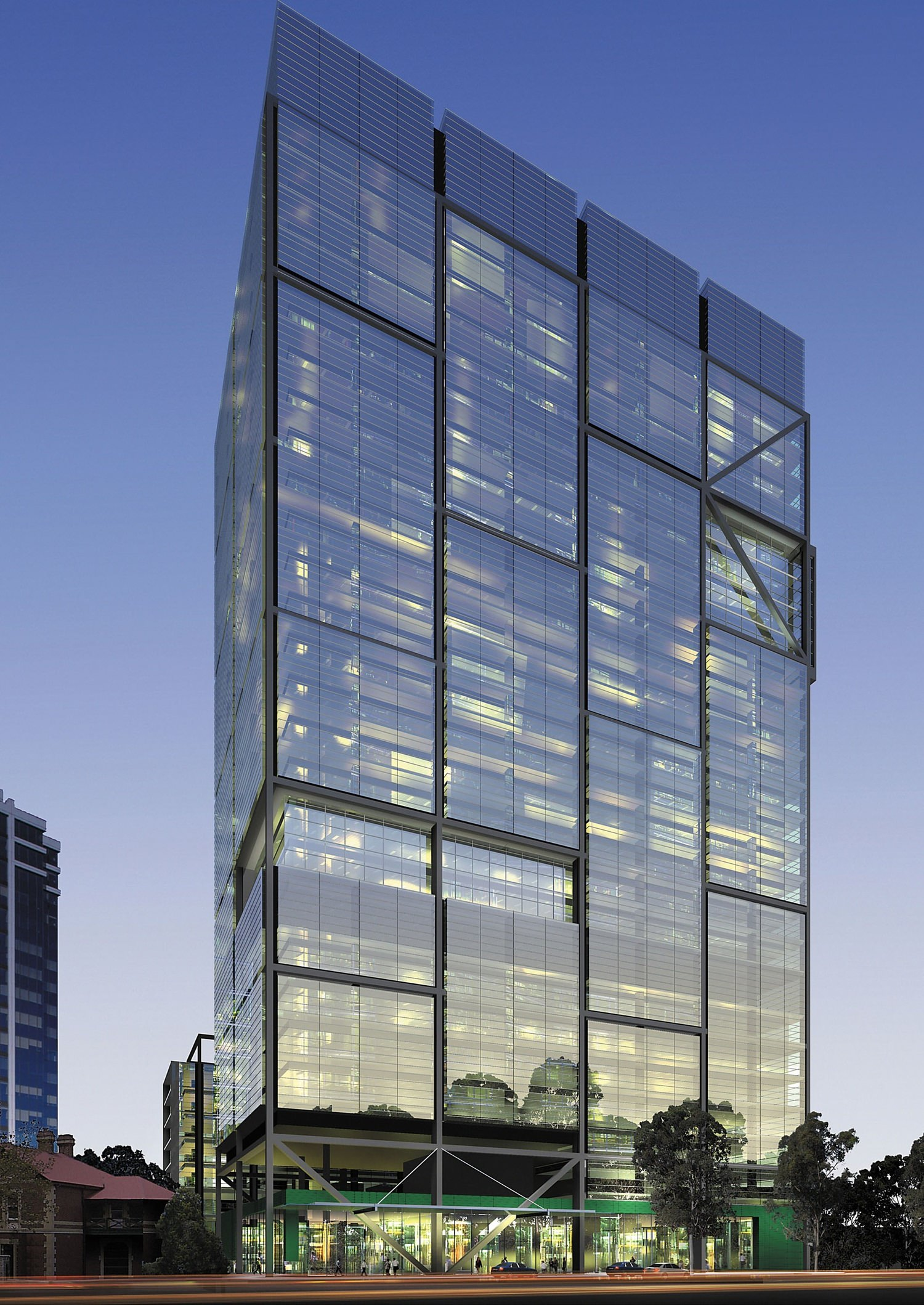 A large building that has very large glass panels on it and there are some trees at the base of it.