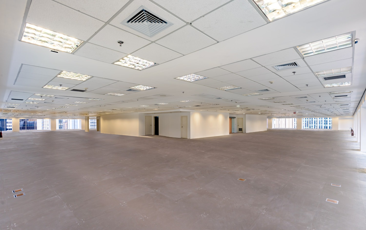 An empty office building that has a white drop ceiling and concrete flooring as well as lighting in the ceiling.