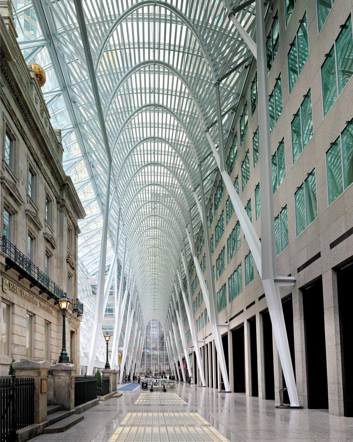 A covered walkway between a modern and a historic building.
