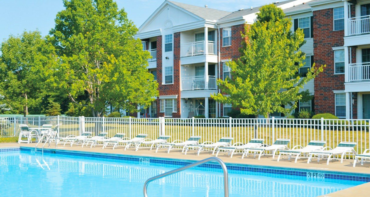A swimming pool that has chairs lining the area with an apartment building in the background.