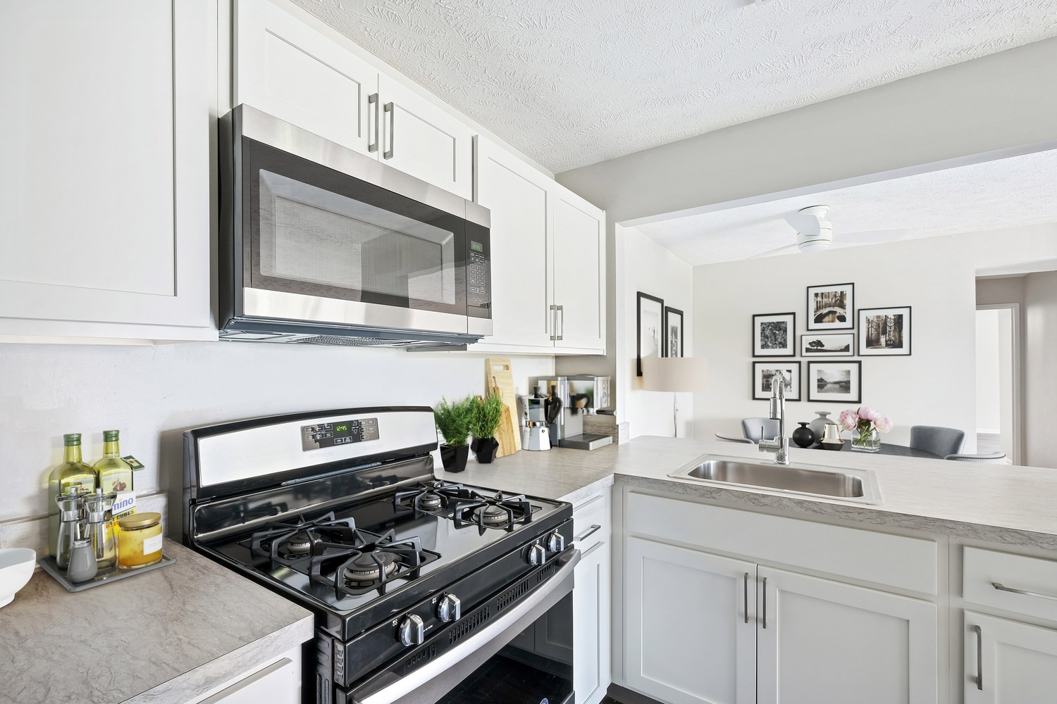 A kitchen that has a gas range in the middle of it, a microwave above it, and white cabinets with pulls on them.